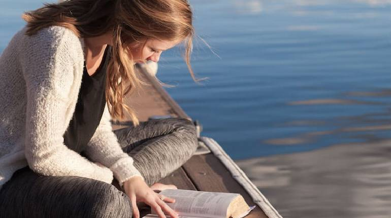 Image That Shows A Lady Reads a Book Sitting in a Beach