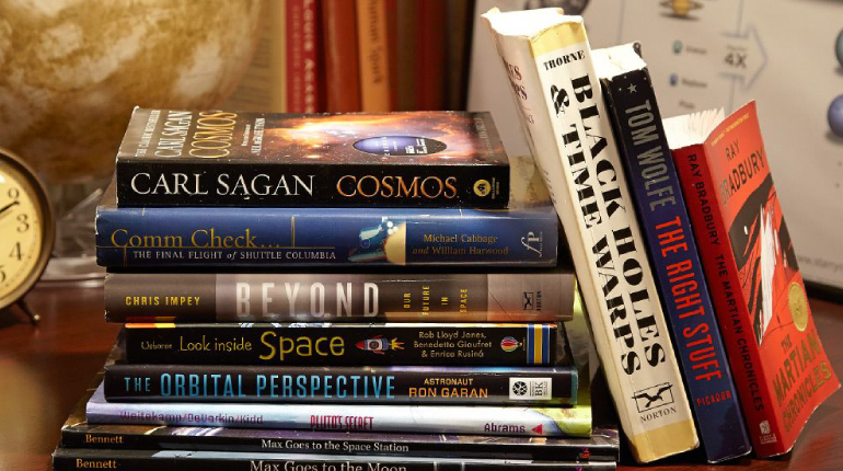 A Pile Of Books About Space Placed On The Table.