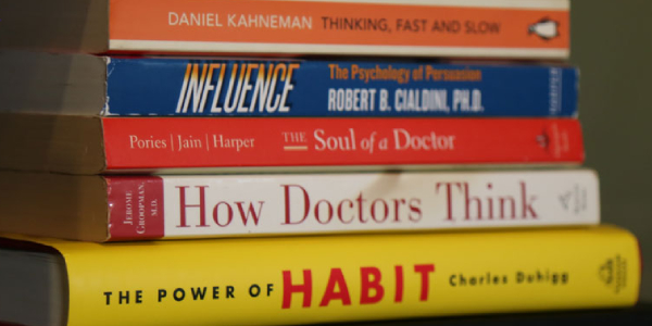 A Pile Of Books About Behavioural Science Placed On The Table.